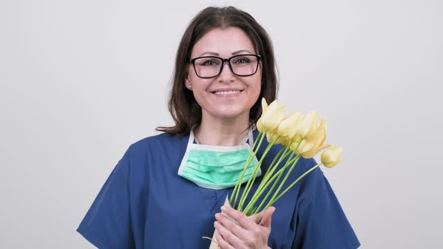Woman doctor nurse in protective medical mask with bouquet of flowers on white background. Woman doctor nurse in protective medical mask with bouquet of flowers on white background. Doctor's Day, World Health Day, National Nurses Day. High quality 4k footage world health day stock videos & royalty-free footage