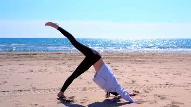 Woman does Downward Facing Dog pose in yoga on sea sand beach sport exercise. video
