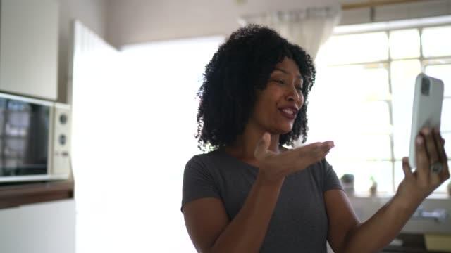 kvinna gör ett videosamtal hemma med hjälp av mobiltelefon - saknad känsla bildbanksvideor och videomaterial från bakom kulisserna