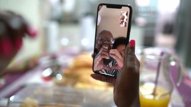frau macht einen video-chat auf handy auf frühstück zu hause - smartphone mit corona app stock-videos und b-roll-filmmaterial