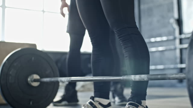 frau macht front kniebeugen mit trainer - trainingsraum freizeiteinrichtung stock-videos und b-roll-filmmaterial