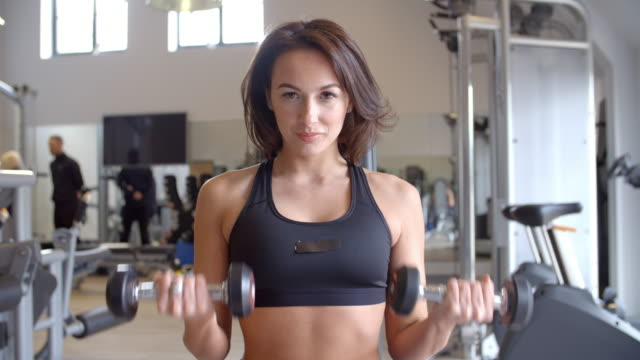 Woman doing bicep curls with dumbbells at a gym, front view, shot on R3D video