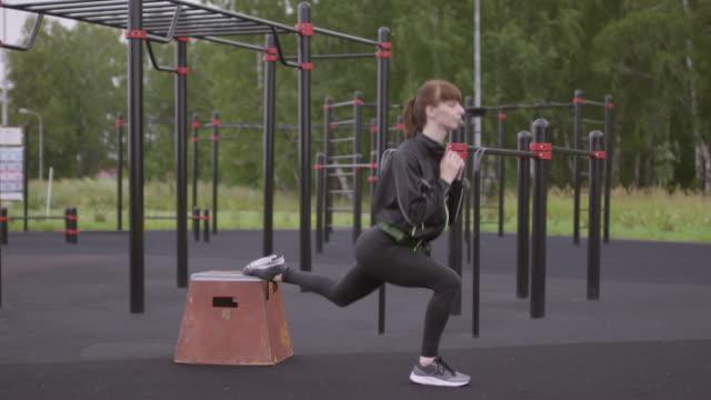 vídeos de stock e filmes b-roll de woman doing bulgarian split squat exercise at outdoor fitness court - agachar se