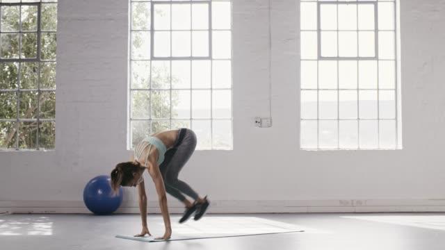 woman doing cobra and downward facing dog pose in yoga studio - metodo pilates video stock e b–roll