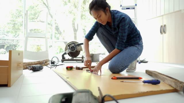 vídeos de stock e filmes b-roll de woman doing diy work, assembling furniture at home - bricolage