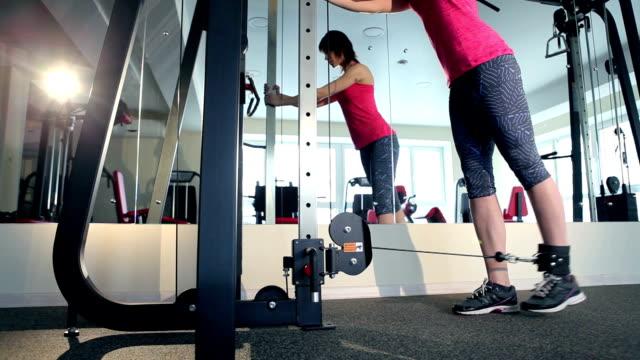 makine vasıl jimnastik salonu ile egzersiz yaparak kadın - i̇nsan sırtı stok videoları ve detay görüntü çekimi