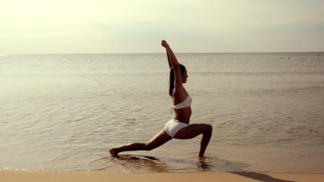 woman doing exercises in the beach - endast unga kvinnor bildbanksvideor och videomaterial från bakom kulisserna