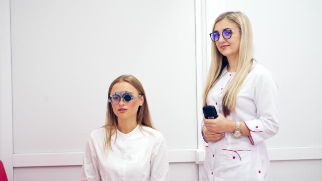 vidéos et rushes de femme faisant l'essai d'oeil dans la clinique - réfracteur