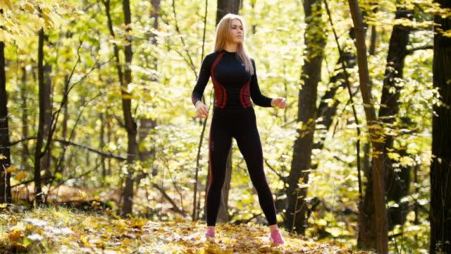 kvinnan gör fitnessövningar utomhus. kvinna stretching hennes armbågar i höst skog. smal tjej på utomhus träning - tävlingsdistans bildbanksvideor och videomaterial från bakom kulisserna