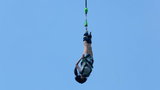 woman doing fun and fear adventure bungee jumping from high up - bungee jumping video stock e b–roll