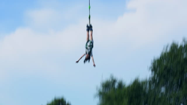 Woman doing fun and fear adventure bungee jumping from high up