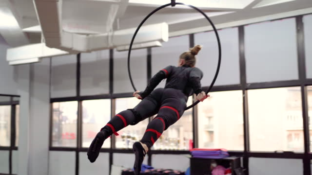Woman doing gymnastic exercises on the ring