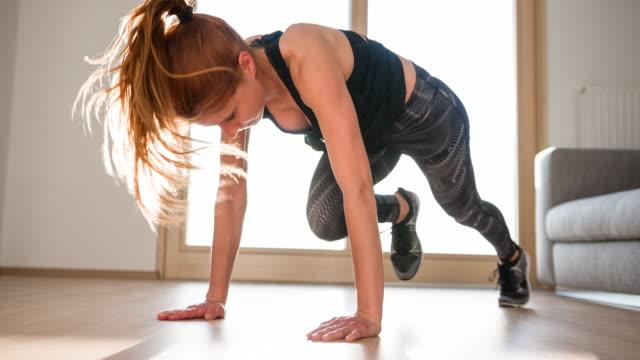 vídeos de stock e filmes b-roll de woman doing home workout in living room - treino em casa