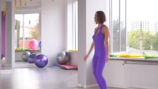Woman doing jumping jacks at gym