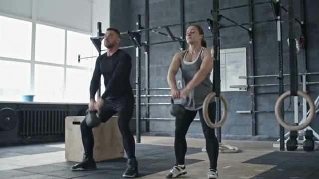 woman doing kettlebell snatch with personal coach - giria filmów i materiałów b-roll