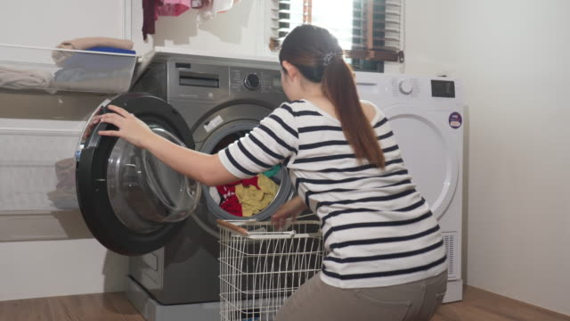 Woman doing laundry and loading clothes into washing machine 4k footage of Woman doing laundry and loading clothes into washing machine laundry basket stock videos & royalty-free footage