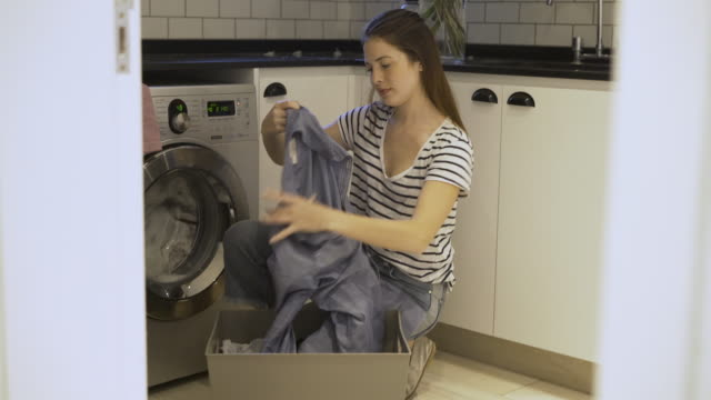 Woman doing laundry Medium shot of woman doing laundry at home less than 10 seconds stock videos & royalty-free footage