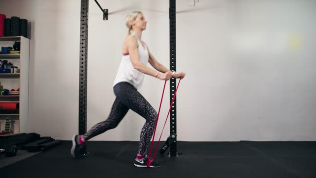 Woman doing lunges while holding on resistance band and raising her arms video