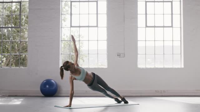 woman doing plank twist at fitness studio - metodo pilates video stock e b–roll