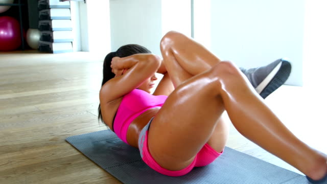 Woman doing press on mat in gym. Girl twisting elbow to the knee in the gym video