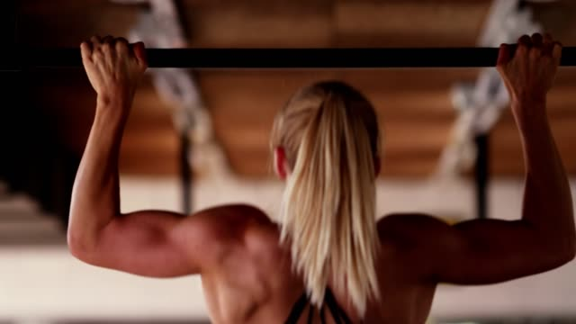 Woman doing pull ups Rear view of athletic woman doing pull ups in the gym. push ups stock videos & royalty-free footage