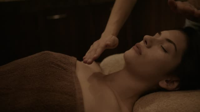 Woman doing reiki alternative medicine treatment at holistic therapy spa Woman lying down and relaxing with reiki holistic therapy treatment by alternative medicine professional therapist massage oil stock videos & royalty-free footage