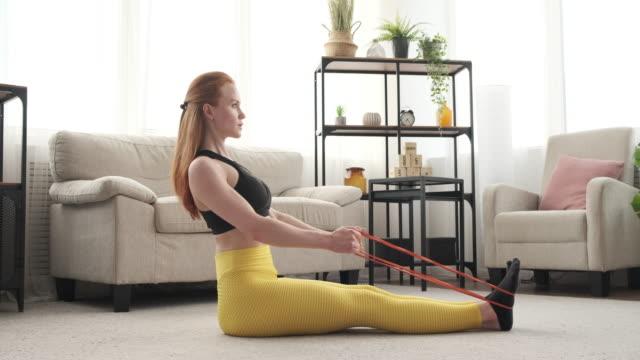 kvinna gör sittande rad övning med resistance band - styrketräning bildbanksvideor och videomaterial från bakom kulisserna