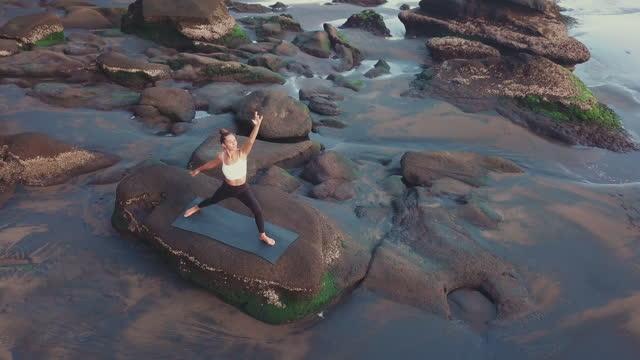 donna che fa sport su rocky shore - posizione corretta video stock e b–roll