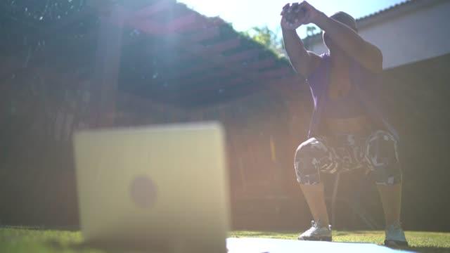 frau macht kniebeugen während des virtuellen übungsunterrichts zu hause - fitnesskurs stock-videos und b-roll-filmmaterial