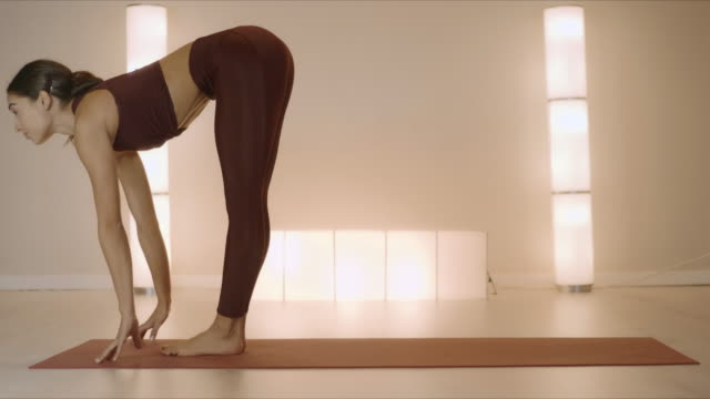 woman doing standing forward bend pose on mat. girl stretching in yoga studio - inarcare la schiena video stock e b–roll