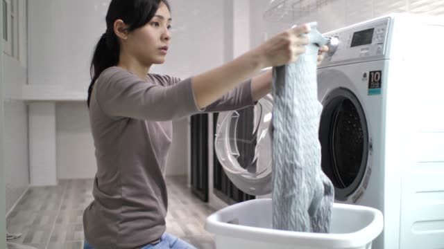 Woman doing the laundry with Washing Machine at home