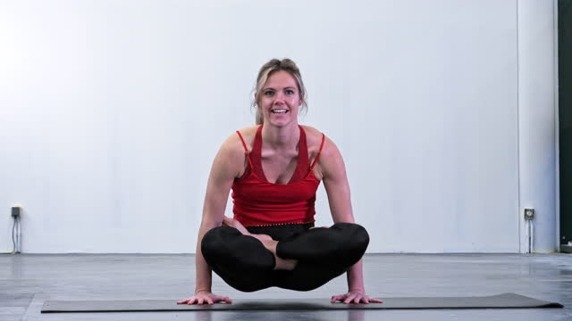 Woman doing yoga at gym in floating lotus position on hands, scales pose