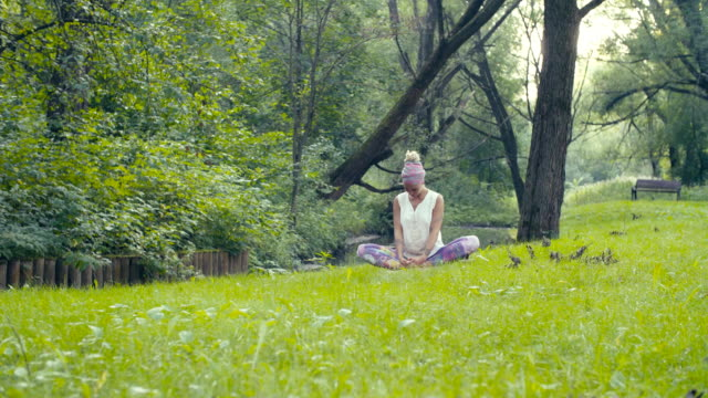 Woman doing yoga exercises near the river Attractive woman doing yoga exercises near the river in a park. Gold time shooting russian ethnicity stock videos & royalty-free footage
