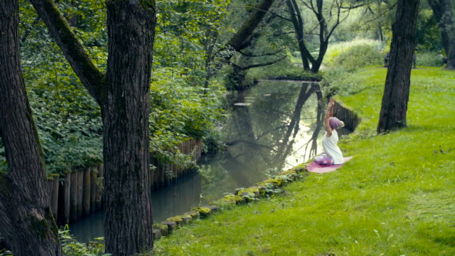 Woman doing yoga exercises near the river High angle view. Attractive woman doing yoga exercises near the river in a park. Gold time shooting russian ethnicity stock videos & royalty-free footage