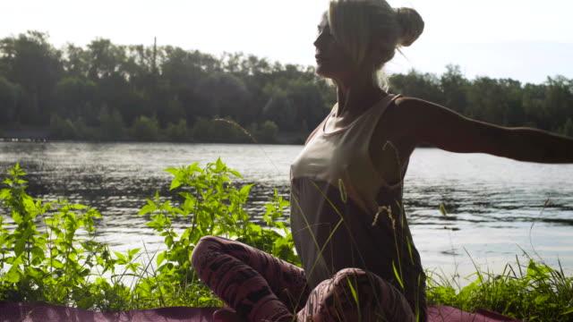 woman doing yoga exercises on the river bank - posizione corretta video stock e b–roll