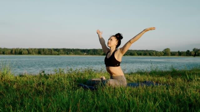 vídeos y material grabado en eventos de stock de mujer haciendo yoga en la mañana en el lago. linda chica en posición de loto al amanecer - posición descriptiva