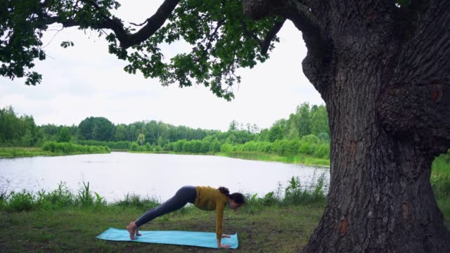 Woman doing yoga near the old oak by the lake