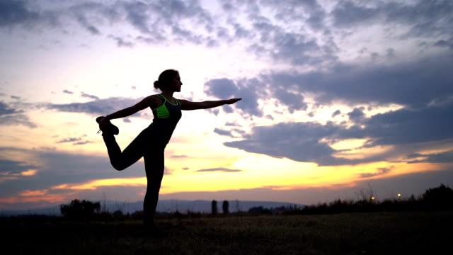 여자 하기 요가 에 초원 - mindfulness 스톡 비디오 및 b-롤 화면