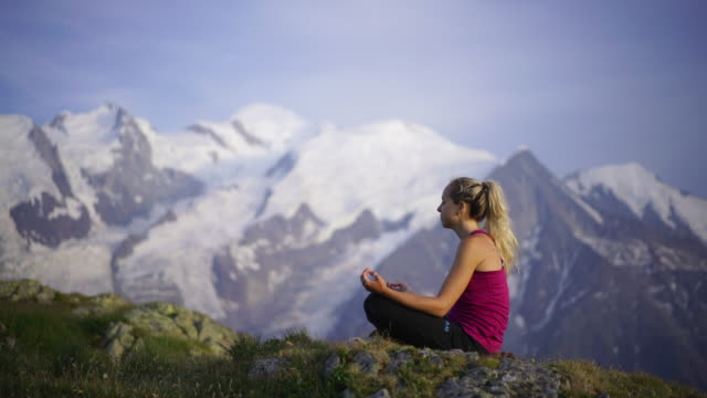 woman doing yoga on mountain top at sunset - monte bianco video stock e b–roll