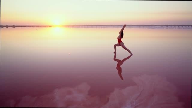 vidéos et rushes de femme faisant le yoga sur le lac salé rose en ukraine - lac salé