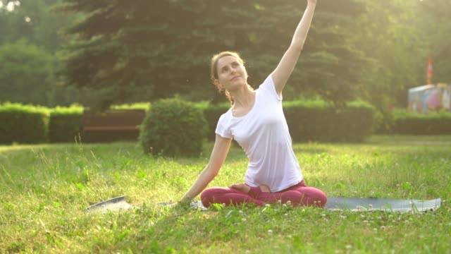 kvinnan gör yoga utomhus - korslagda ben bildbanksvideor och videomaterial från bakom kulisserna