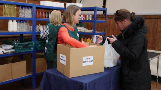vídeos y material grabado en eventos de stock de 4k: bolso donar mujer de abarrotes / alimentos en un banco de alimentos o de alimentos - food drive