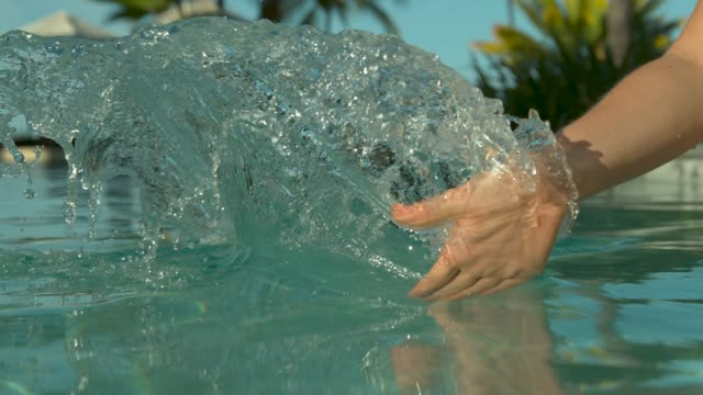 close up: woman drags her hand through calm pool water and creates a ripple. - palm of hand stock videos & royalty-free footage