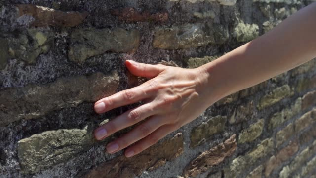 woman draw hand against old red brick wall in slow motion. female hand touch rough surface of stone - mattone video stock e b–roll