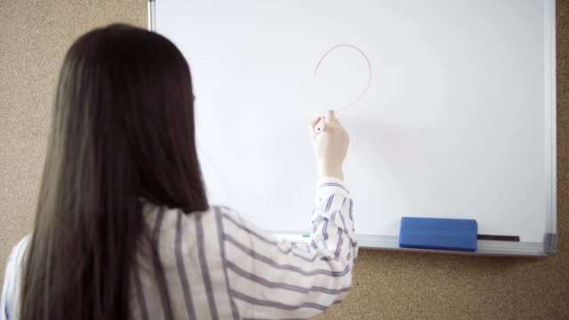 Woman drawing big heart on a whiteboard video