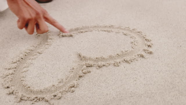 Woman drawing heart shape on sand with finger