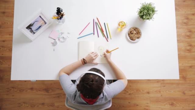 woman drawing picture in notebook at home desk - matita colorata video stock e b–roll