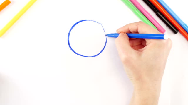 Woman drawing the glasses using black felt-tip pen on white paper, time lapse video