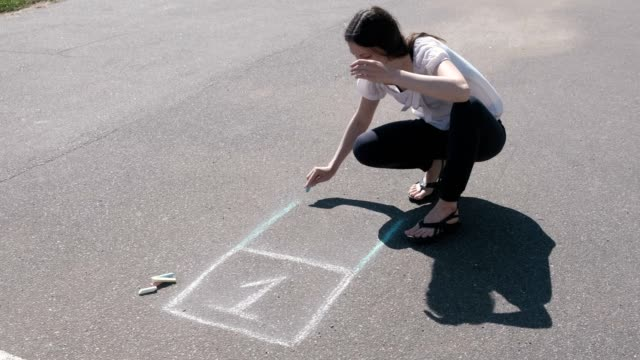 Woman draws a hopscotch on the asphalt with colorful chalks. Woman draws a hopscotch on the asphalt with colorful chalks outdoor play equipment stock videos & royalty-free footage