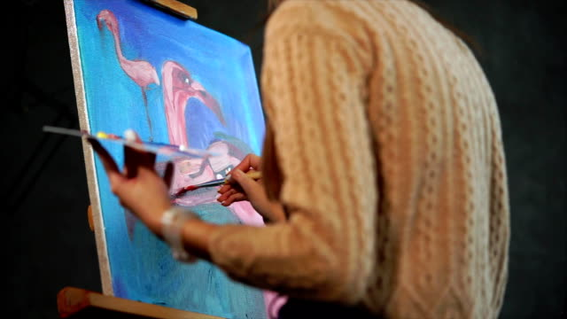A woman draws flamingos in different angles, in her hand is a palette with paint video